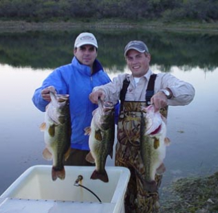 Derek Stratton and Bradford Bryant hold 3 nice bass being transferred from the large lake to the small lake at San Saba Waco Creek Ranch